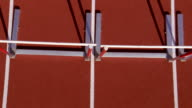 Two athletes jump over hurdles.
