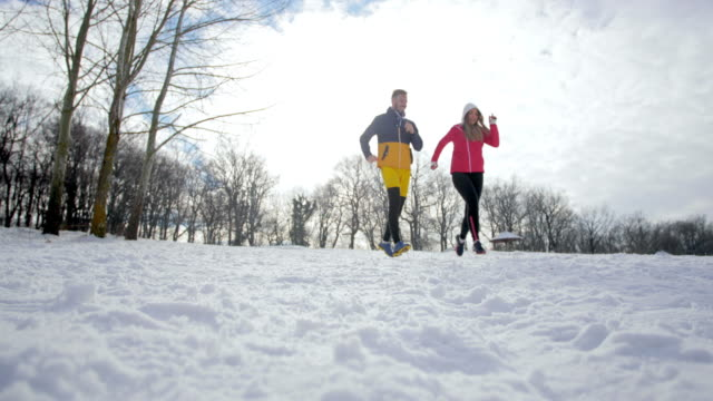 Two athletic couples running on a snow while exercising in nature during winter season.