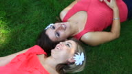 Two attractive girls laying on grass