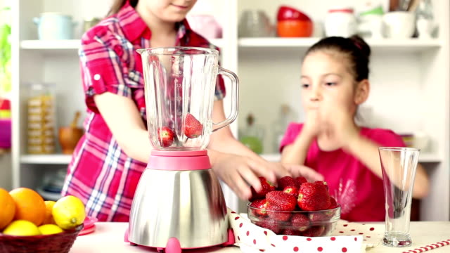 Two Beautiful Little Girls Preparing A Strawberry Smoothie