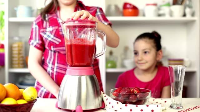 Due belle bambine preparare un Frullato alla fragola