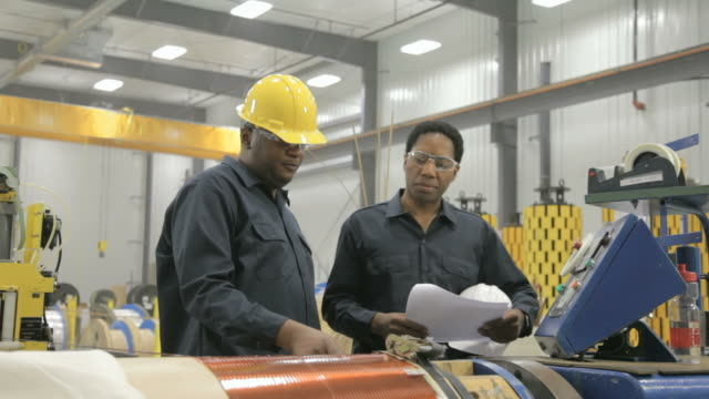 Two black male factory workers discussing paperwork