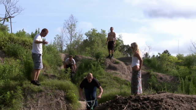 SLO MO WS Two BMX bikers jumping over hill, friends watching / Jacksonville, Florida, USA