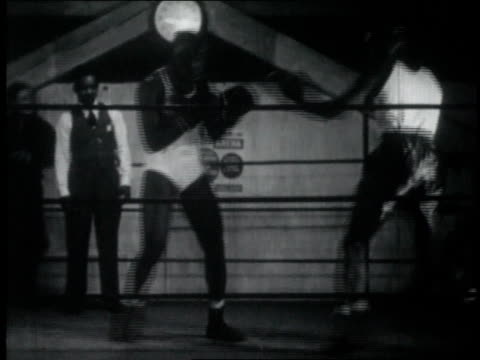 Two boxers compete in the boxing ring as someone observes from the side / United States