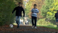 LA WS Two boys ambling down path in park kicking soccer ball while people jog past / London, England