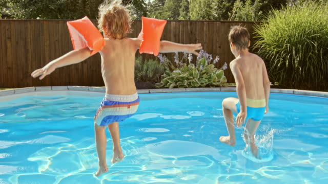 SLO MO DS twee jongens springen in het zwembad in de zon