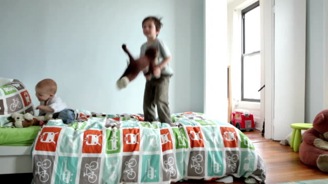 WS Two boys (17 months, 4-5 years) jumping on bed in bedroom / Brooklyn, New York City, USA