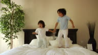 MS, Two boys (18-23 months, 6-7) jumping on bed