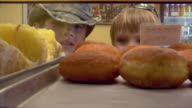 CU, Two boys (8-9, 10-11) looking at pastries in bakery display cabinet, Provincetown, Cape Cod, Massachusetts, USA