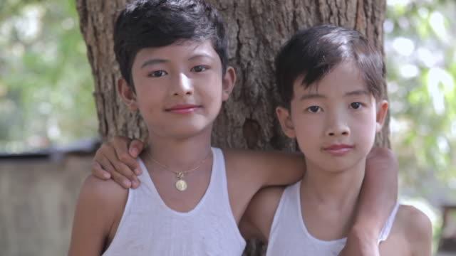 MS two boys looking happily towars arm in arm in front of tree / Bagan, Mandalay Division, Myanmar