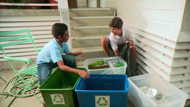 MS Two boys (9-12) organizing bottles into recycle bins, Panama City, Panama