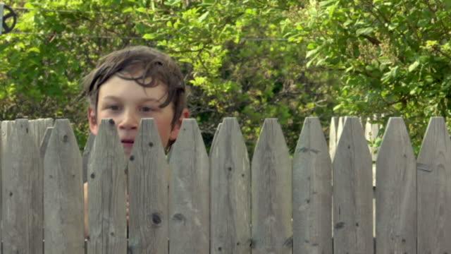 CU, Two boys (8-9, 10-11) peeking over wooden fence, Truro, Caped Cod, Massachusetts, USA