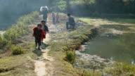 SLO MO WS Two boys running on footpath along riverbank and laughing, Yuanyang, Yunnan, China