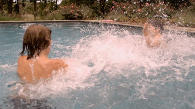 SLO MO MS two boys splashing in swimming pool/Connecticut, USA