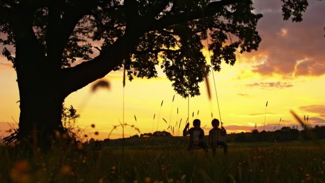 RALLENT due ragazzo ondeggiare sull'Altalena al tramonto