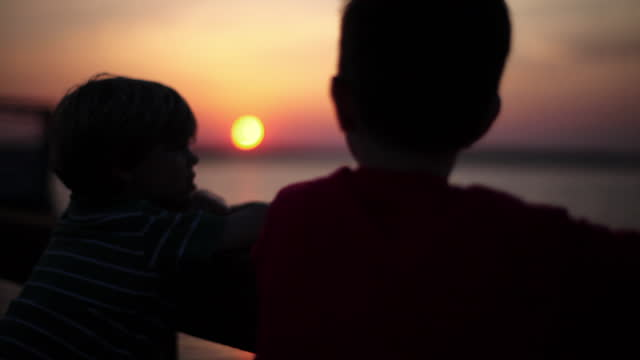Two boys watch the colorful sky from an ocean dock.