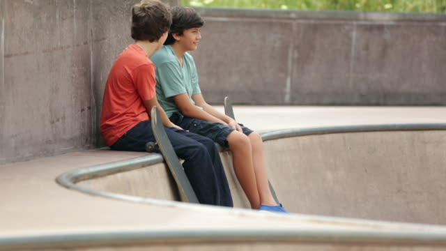 WS Two boys with skateboards at a skateboard park.