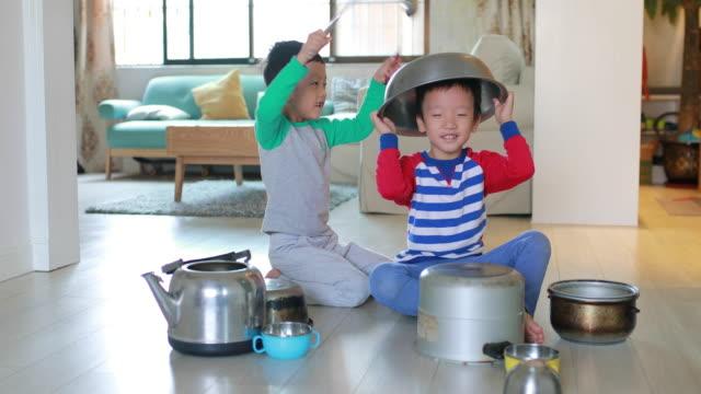 Två bror spelar på golvet med kastruller och stekpannor