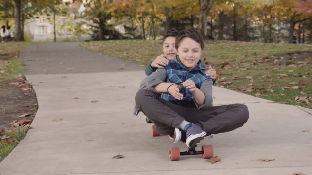 Two Brothers Riding an Electric Skateboard in a Park