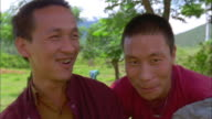 Two Buddhist monks smile at camera, Bhutan Available in HD.