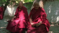 Two Buddhist monks wearing traditional robes sit side by side looking at camera, Tibet Available in HD.