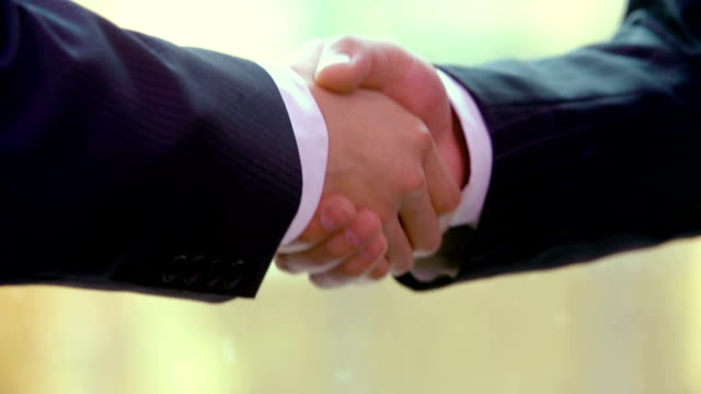 Two buinessmen close deal with a handshake
