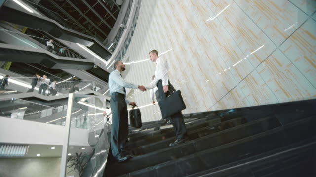 DS Two business men shake hands on the stairs