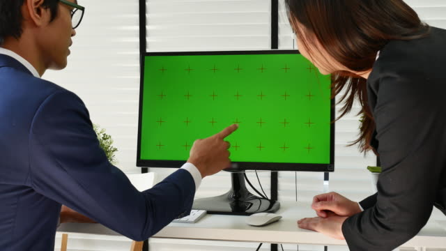 Two Business people Talking to Computer monitor with Green screen, Chroma key