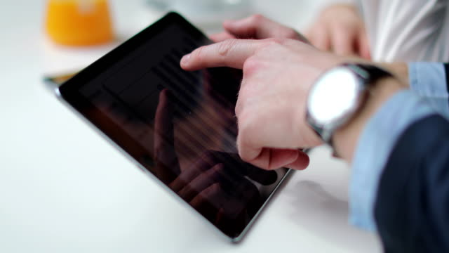 Two business people using digital tablet on coffee break
