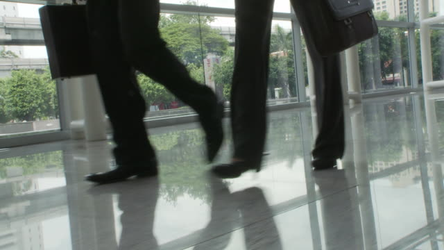 LA DS Two business people walking through lobby area / Bangkok, Thailand