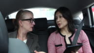 Two business women in the back of a cab.