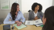 Two business women talk to a third woman across desk
