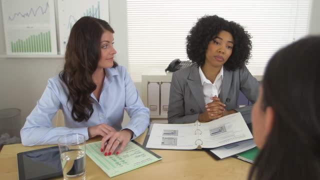 Two business women talk to a third woman across desk