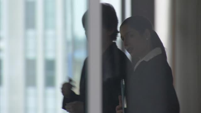 MS PAN Two business women walking and talking in office corridor / London, United Kingdom
