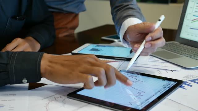 Twee zakenman discussie een zakelijk project in vergadering op digitale Tablet PC- en grafiek papier