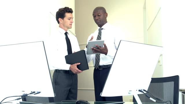 Two businessmen discussing digital tablet