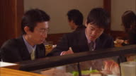 CU, Two businessmen eating sushi in bar