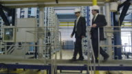 MS LA, two businessmen entering frame right on gangway in industrial installation, pausing in front of camera and shaking hands; then descending steps to camera and exit frame left, RED R3D 4K
