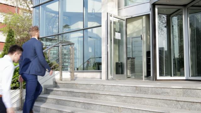 Two businessmen entering office building