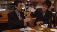 MS, Two businessmen having meeting in Japanese restaurant, one pouring beer