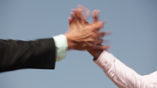 Two businessmen holding hands