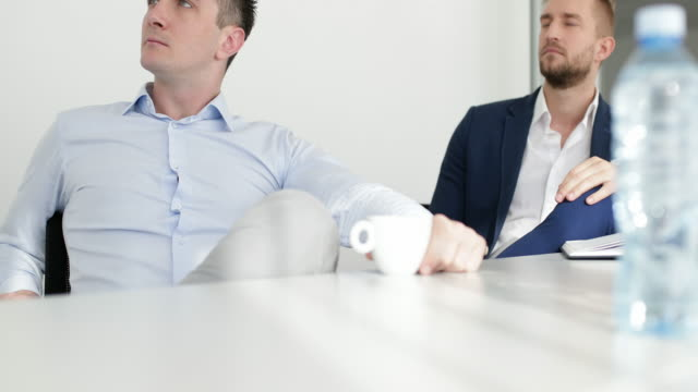Two businessmen listening colleague in office
