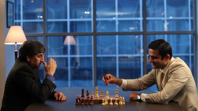 Two businessmen playing chess