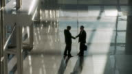 WS HA Two businessmen shaking hands in lobby / Bangkok, Thailand