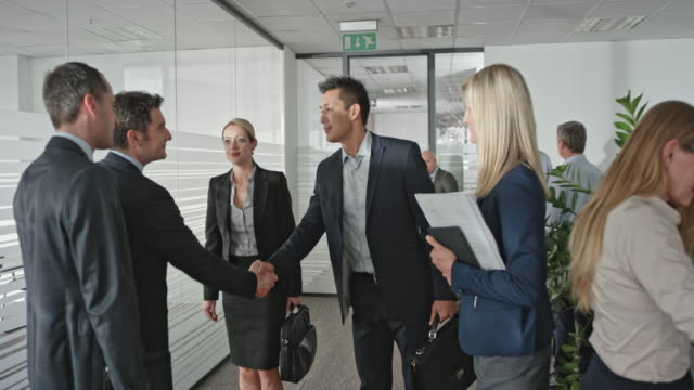 Two businessmen shaking hands with a businesswoman and an Asian businessman before they enter the meeting room.