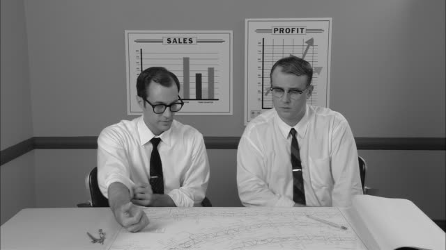 B/W MS Two businessmen sitting at table  looking at architectural plans and discussing them/ New York City