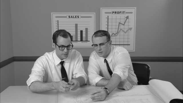 B/W MS Two businessmen sitting at table  looking at architectural plans/ Man measuring with protractor as they talk/ New York City