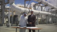 MS Two businessmen standing near blueprint and laptop outside oil refinery / Vista del Mar, California, USA