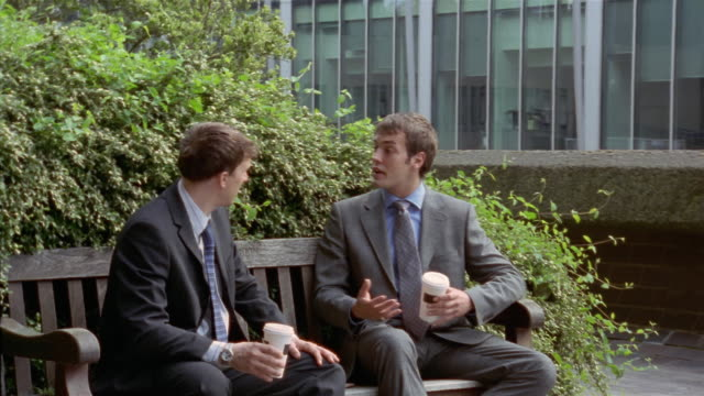 Two businessmen taking coffee break on bench outside office building / one of them answering cell phone / hanging up and leaving / London, England