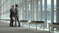 SLO MO WS Two businessmen talking in office building hallway, Cape Town, South Africa